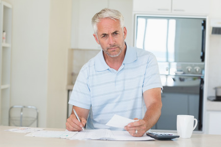Serious man working out his finances at home in the kitchen Stock Photo - 27161796