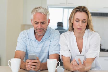 not talking: Distante coppia seduta al bancone sms e non parlare a casa in cucina