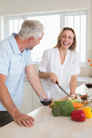 Laughing couple making dinner together at home in the kitchen photo