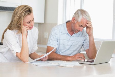 Worried couple working out their finances with laptop at home in the kitchen