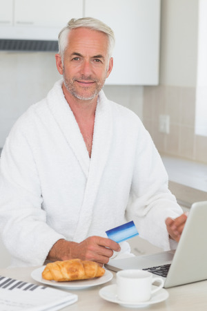 Happy man shopping online at breakfast in a bathrobe at home in the kitchen photo