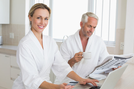 Couple shopping online and reading newspaper in bathrobes  at home in the kitchen photo
