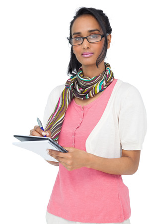 unsmiling: Portrait of a cool young woman writing in notepad over white background Stock Photo