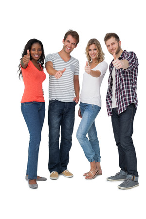 casually: Full length of casually dressed young people gesturing thumbs up over white background