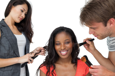 Assistants applying make-up to a female model over white background photo