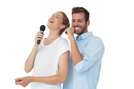 Cheerful couple singing into microphones over white background photo