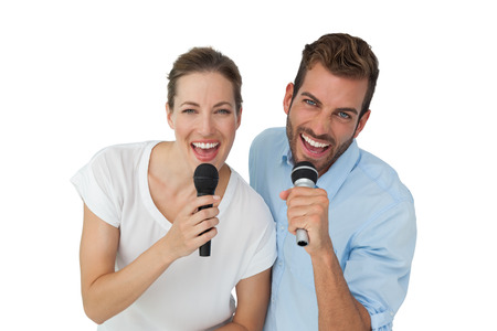 Portrait of a cheerful couple singing into microphones over white background photo