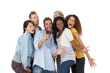 Group of happy people singing into microphone over white background photo