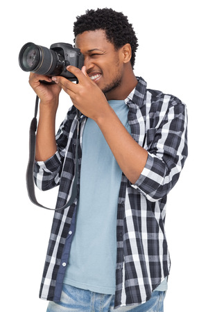 over white background: Young man with camera standing over white background