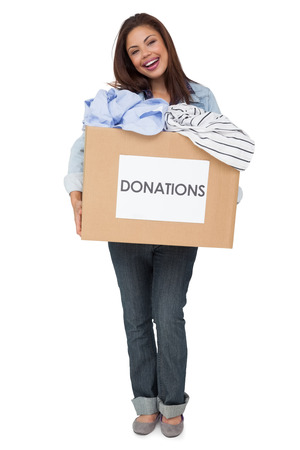 Portrait of a happy young woman with clothes donation standing over white background photo