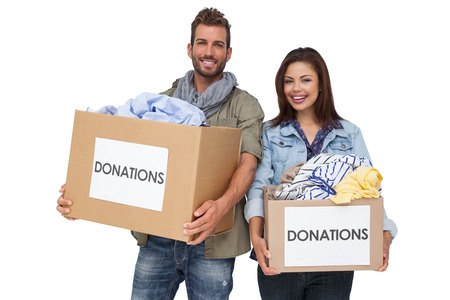 Portrait of a happy young couple with clothes donation standing over white background photo