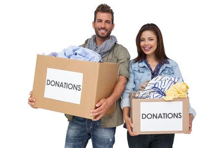 altruismo: Retrato de una joven pareja feliz con la donaci�n de ropa de pie sobre fondo blanco