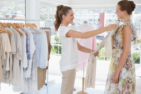 kledingwinkel: Zijaanzicht van een verkoopster bijstaan vrouw met kleren bij de kledingwinkel