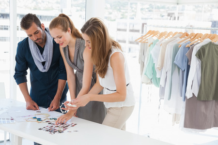 fashion industry: Group of fashion designers discussing designs in a studio