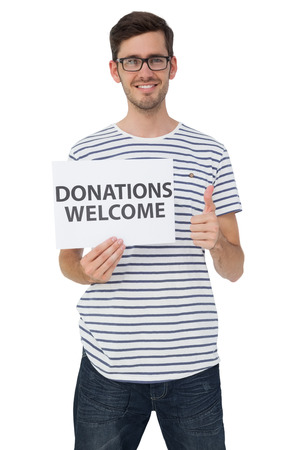 Portrait of a happy young man holding a donation welcome note while gesturing thumbs up over white background photo