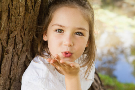 Close-up portrait of a pretty young girl blowing a kiss at the park photo