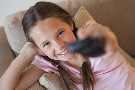 changing channels: Portrait of a young girl changing channels in the living room at home Stock Photo
