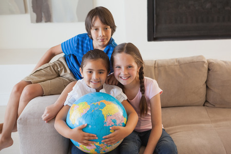 Portrait of happy young kids with globe sitting in the living room at home photo
