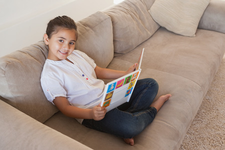storybook: Side view portrait of a relaxed girl reading storybook on sofa in the living room at home Stock Photo