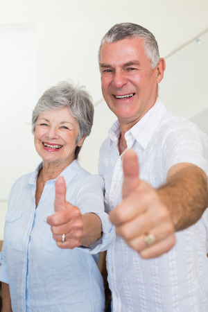 Cheerful retired couple looking at camera giving thumbs up at home in living room photo