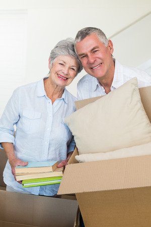 Happy senior couple moving into new home smiling at camera photo
