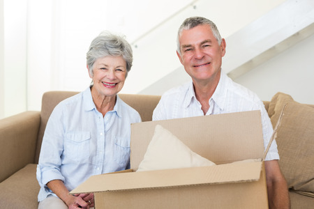moving box: Cheerful senior couple moving into new home smiling at camera Stock Photo