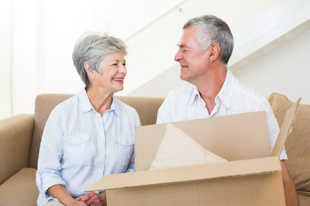 Cheerful senior couple moving into new home smiling at each other photo