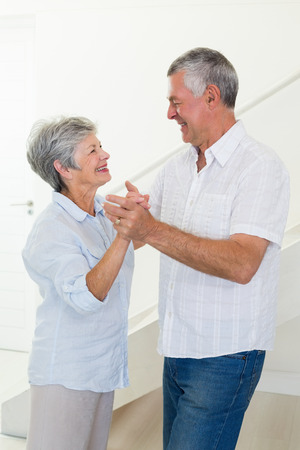 Happy senior couple dancing together at home in living room photo