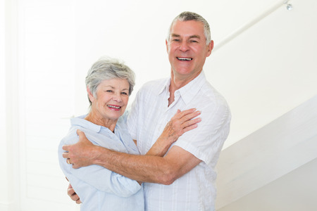 Happy senior couple dancing together at home in living room smiling at camera photo