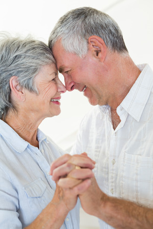 Happy senior couple dancing together head to head at home in living room photo