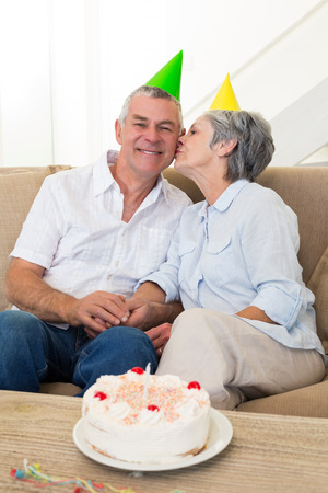 Senior couple sitting on couch celebrating a birthday at home in living room photo