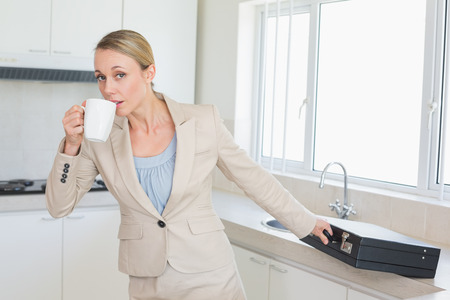 late thirties: Businesswoman rushing out the door to work in the morning at home in the kitchen Stock Photo