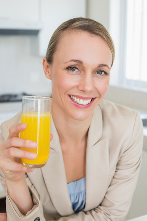 Happy businesswoman having orange juice before work in the morning at home in the kitchen
