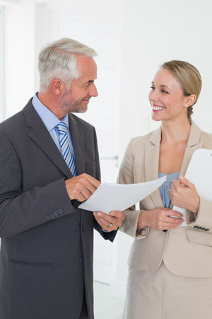 Smiling estate agent going over contract with customer in empty house photo