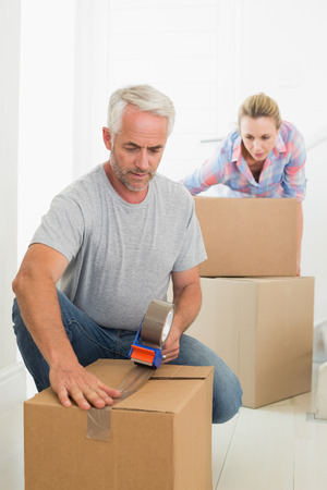 Happy couple sealing cardboard moving boxes in their old home photo