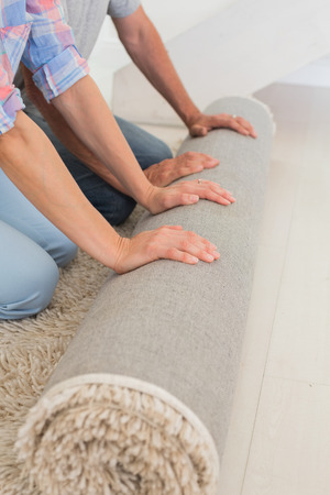 relocating: Couple rolling out new rug in their new home Stock Photo