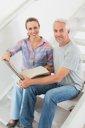 Happy couple picking out carpet samples together in their new home photo