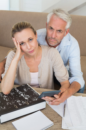 figuring: Serious couple calculating their bills at the couch at home in the living room