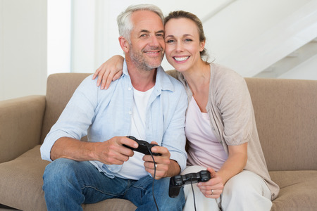 Happy couple having fun on the couch playing video games at home in the living room photo