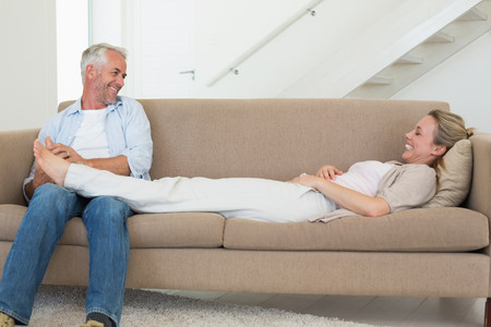Caring man giving his partner a foot rub on the couch at home in the living room photo