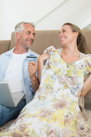 Happy couple shopping online on the couch at home in the living room photo