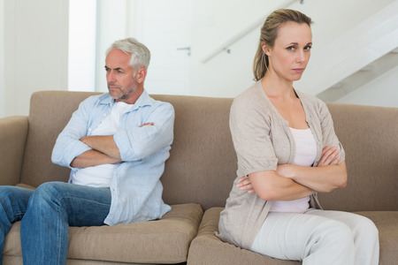 not talking: Angry couple sitting on couch not talking to each other at home in the living room Stock Photo