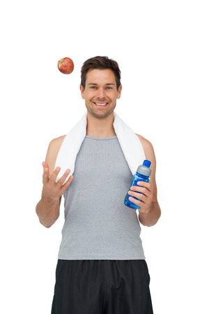Portrait of a smiling fit young man with apple and water bottle over white background photo
