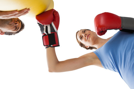 Determined female boxer focused on her training over white background photo