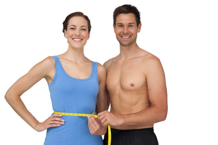 girth: Portrait of a fit young man measuring womans waist over white background Stock Photo