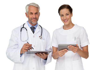 Male and female doctors with digital tablets over white background photo