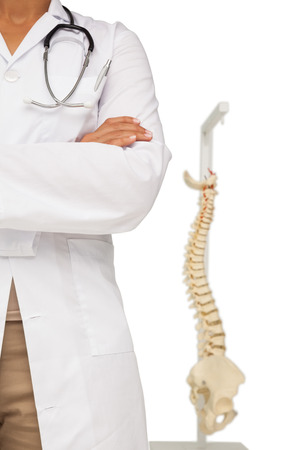 Close-up mid section of a female doctor with skeleton model over white background photo