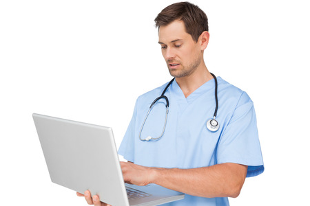 Concentrated male surgeon using laptop over white background photo