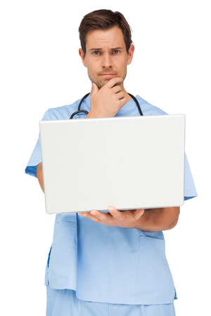 Portrait of a male surgeon using laptop over white background photo