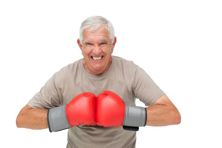 Close-up portrait of a determined senior boxer over white background